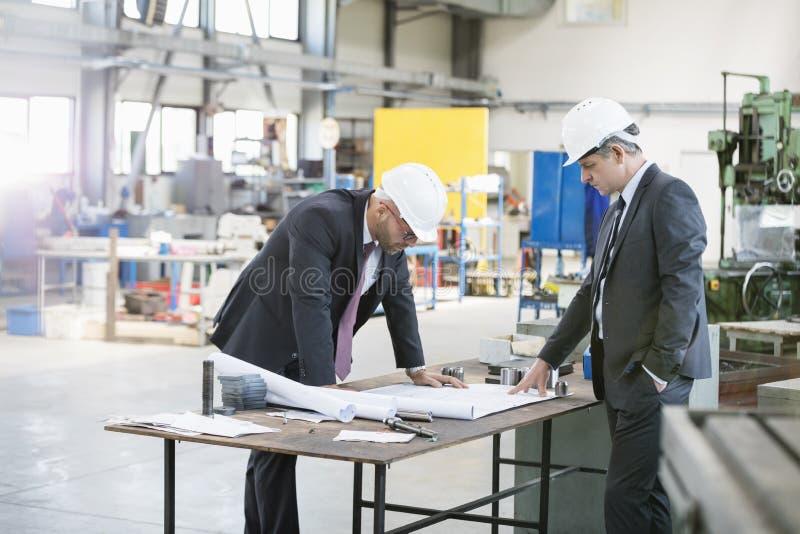 Biznesmeni egzamininuje projekt przy workbench w metalu przemysle zdjęcia stock