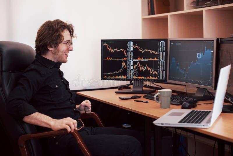 Biznesmeni handluje zapasy online Akcyjny makler patrzeje wykresy, wskaźniki i liczby na wieloskładnikowych ekranach komputerowyc fotografia stock