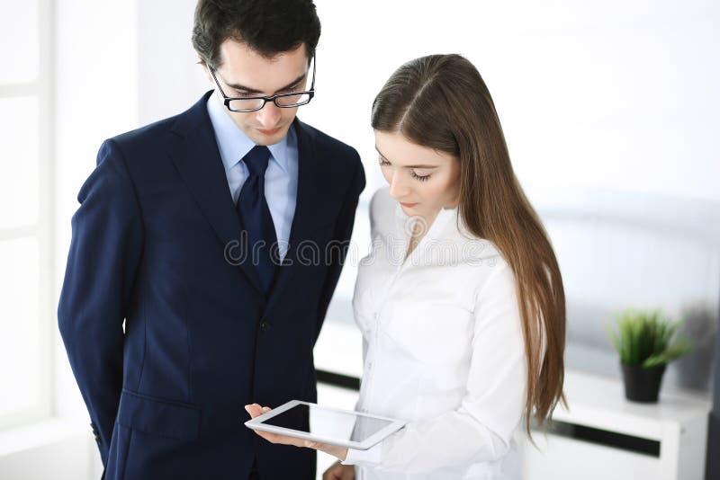 Biznesmeni i kobieta u?ywa pastylka komputer w nowo?ytnym biurze Koledzy lub firma kierownicy przy miejsce pracy partnery zdjęcia royalty free