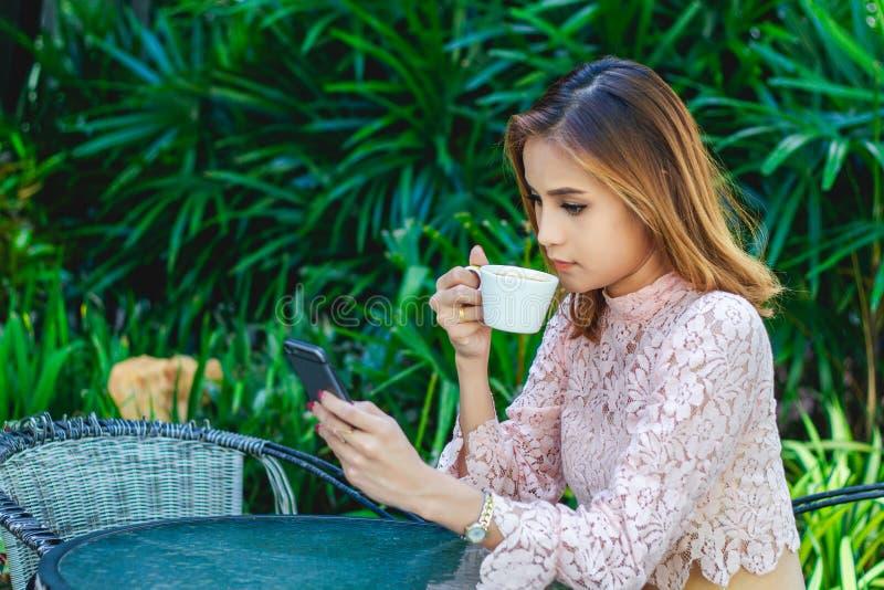 Biznesmeni i kobiety używają wiszącą ozdobę i dotykają mądrze telefon dla komunikacji i sprawdzać na ludzie biznesu w biurze zdjęcie stock