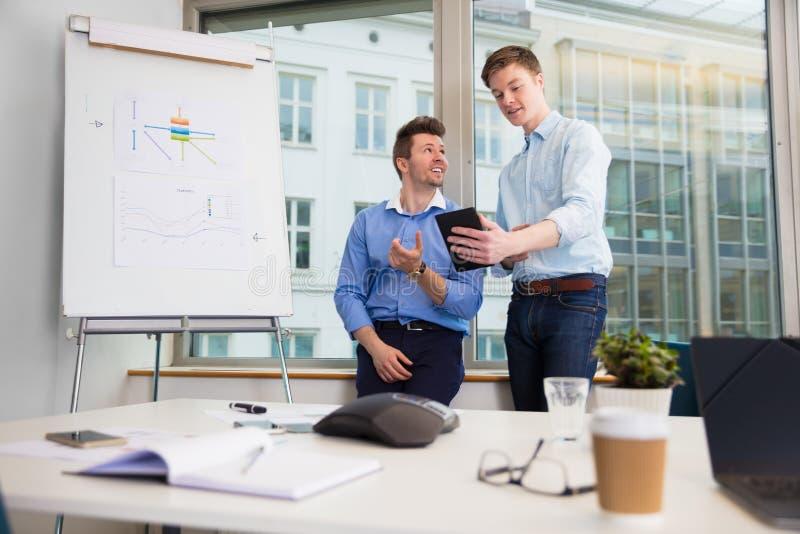 Biznesmeni Komunikuje Nad Cyfrowej pastylką Przeciw okno zdjęcie stock