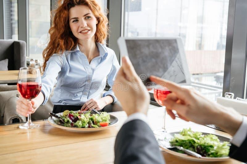Biznesmeni ma biznesowego lunch przy restauracyjną siedzącą łasowanie sałatką pije wino mężczyzny wyszukuje cyfrowego pastylki za obraz stock
