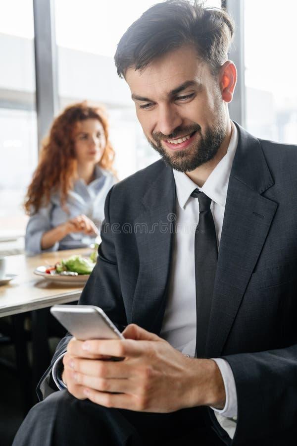 Biznesmeni ma biznesowego lunch przy restauracyjnym obsiadanie mężczyzną w górę wyszukiwać smartphone podczas gdy kobiety łasowan fotografia royalty free