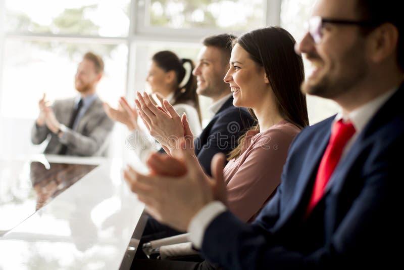Biznesmeni oklaskuje przy biurem podczas gdy w spotkaniu zdjęcia stock
