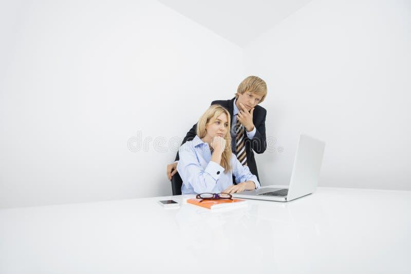 Biznesmeni patrzeje laptop w biurze z ręką na podbródku zdjęcie stock
