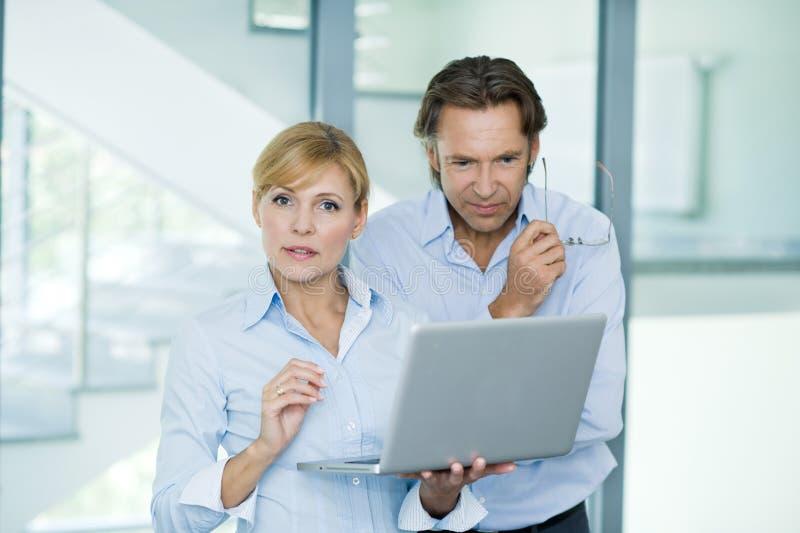 Biznesmeni pracuje z laptopem przy biurem, dyskutuje, copyspace, pomyślny biznes obrazy stock