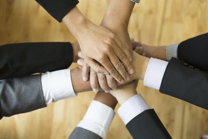 Biznesmeni stawiają ich rękę na górze each inny - praca zespołowa, u fotografia stock