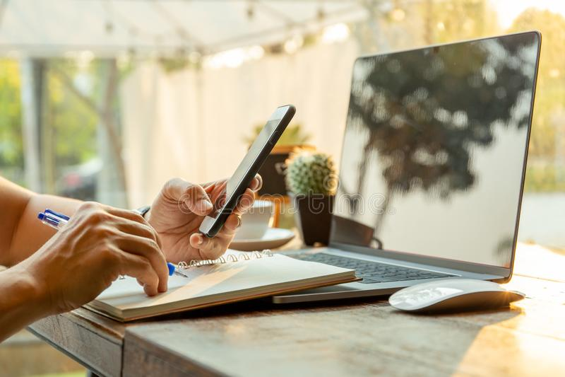 Biznesmeni używa telefony komórkowych i pisać na notatniku z piórem na stole obrazy stock