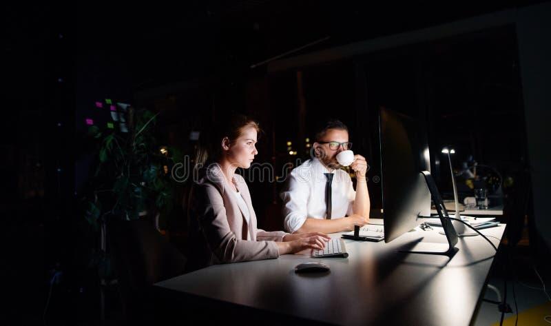 Biznesmeni w biurze przy nocą pracuje póżno zdjęcie stock