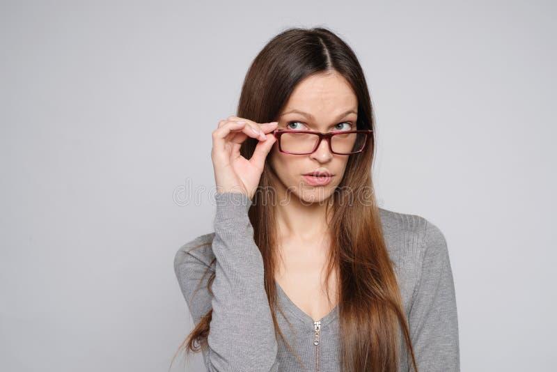 Biznesmenka w okularach patrząca w górę i myśląca. Izolowany obraz stock