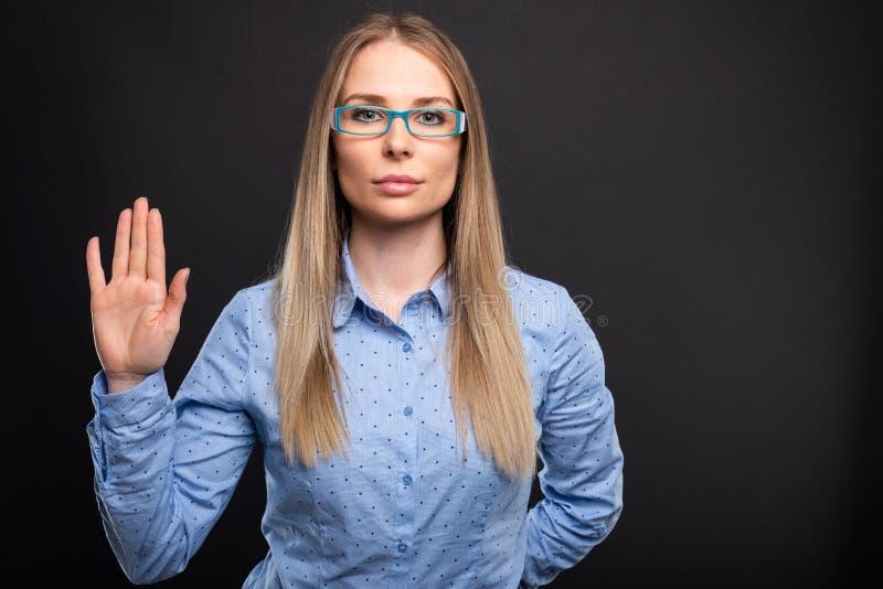 Biznesowa dama jest ubranym błękitnych szkła robi sfałszowanemu ślubowaniu gestykuluje fotografia stock