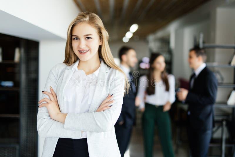 Biznesowa dama z krzyżować rękami przed dyskutować coworkers obrazy royalty free