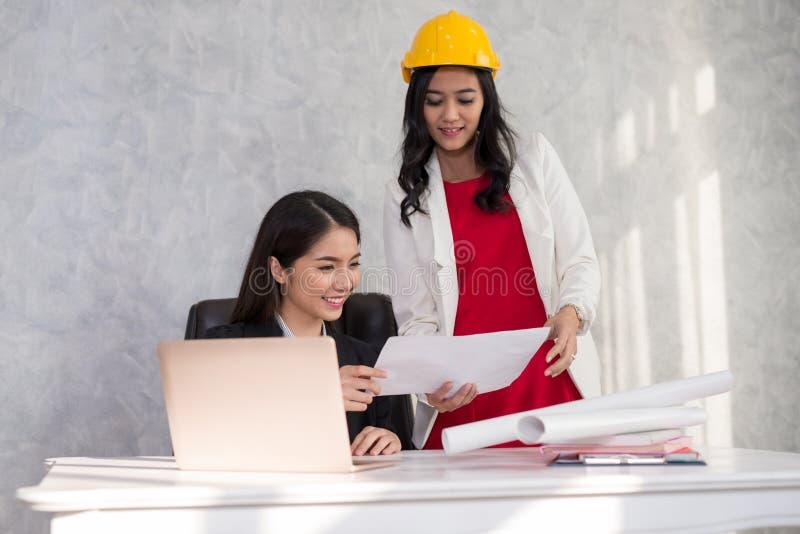 Biznesowa dziewczyna i inżynier z Azjatyckimi ludźmi opowiadamy wokoło a obraz royalty free