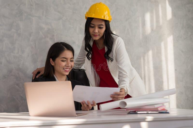 Biznesowa dziewczyna i inżynier z Azjatyckimi ludźmi opowiadamy wokoło a fotografia stock