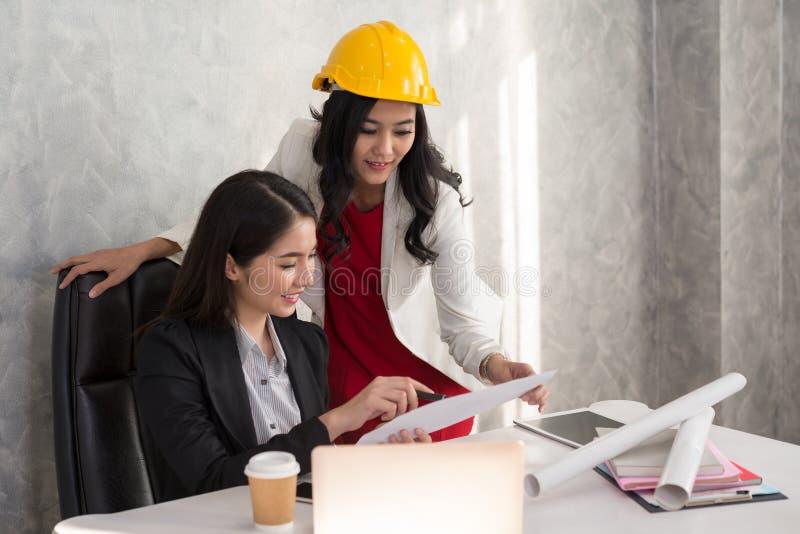 Biznesowa dziewczyna i inżynier z Azjatyckimi ludźmi opowiadamy wokoło a zdjęcia royalty free