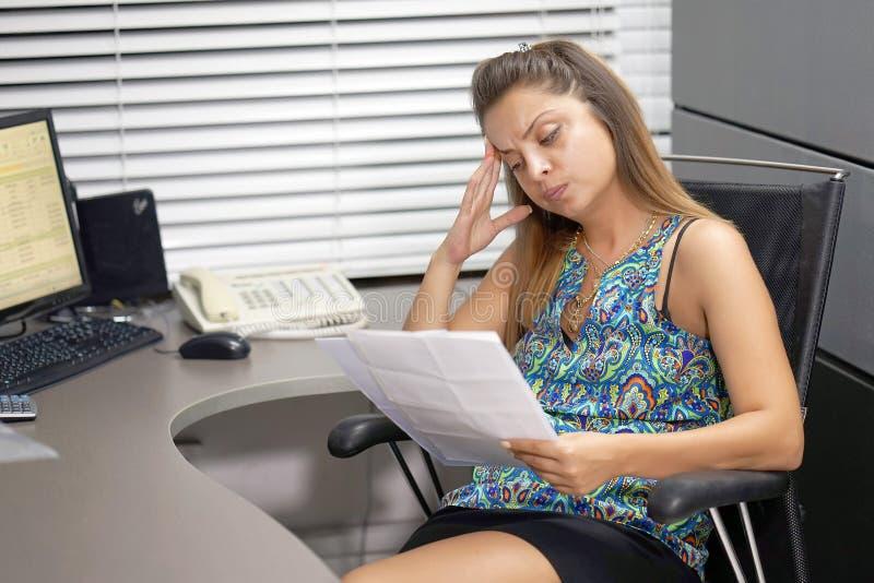 Biznesowa kobieta czyta dokument w biurowym workspace obrazy stock