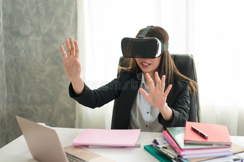 Biznesowa kobieta Dotyka coś przy stołem z vr szkłami ja zdjęcia stock