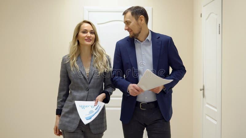 Biznesowa kobieta i mężczyzna chodzimy wzdłuż opowiadać i korytarza obrazy stock
