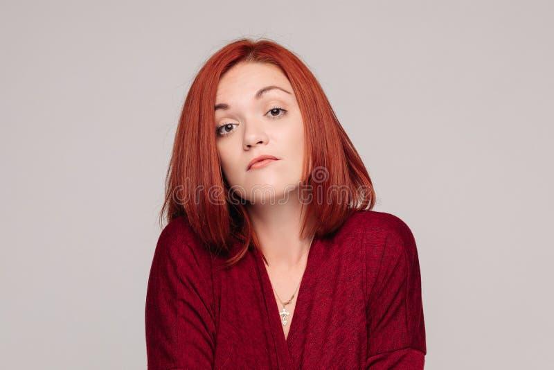 Biznesowa kobieta jest ubranym w czerwieni ma bezwolną emocję i patrzeje udaremniający fotografia stock