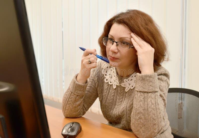 Biznesowa kobieta jest ubranym widowisk spojrzenia w komputerowym monitorze attentively zdjęcie royalty free