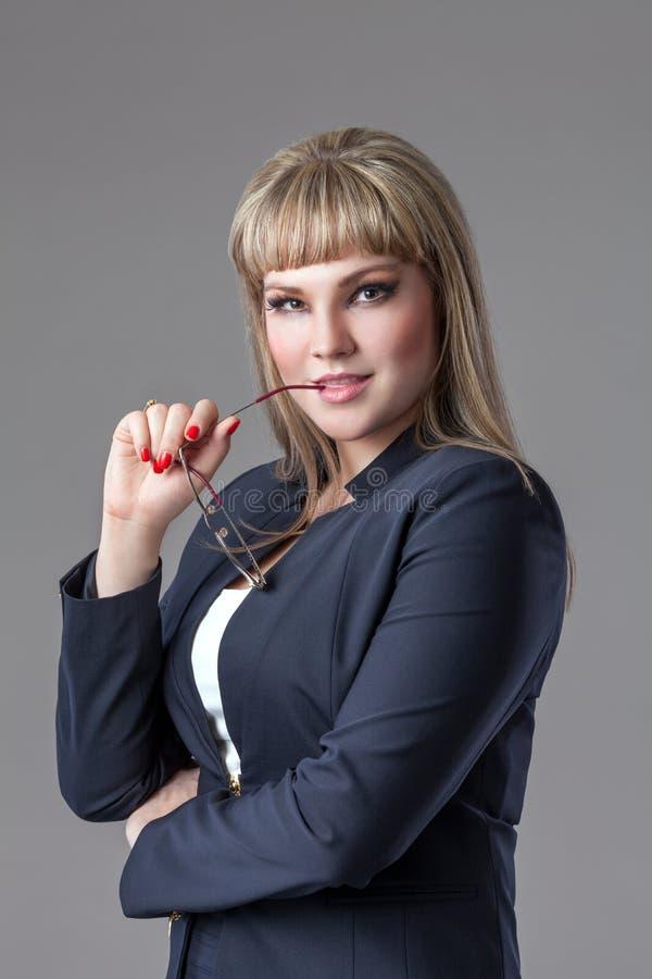 Biznesowa kobieta jest ubranym zmrok z szkłami - błękitny kostium zdjęcie royalty free