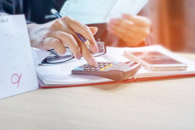 Biznesowa kobieta kalkuluje jej miesięczników rachunki z kalkulatorem obraz stock