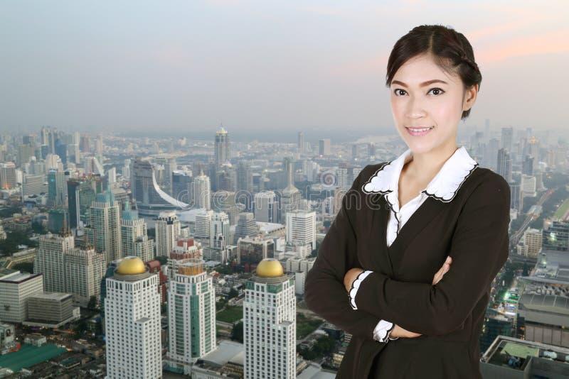 Biznesowa kobieta, krzyżować ręki z miastem, zdjęcie royalty free