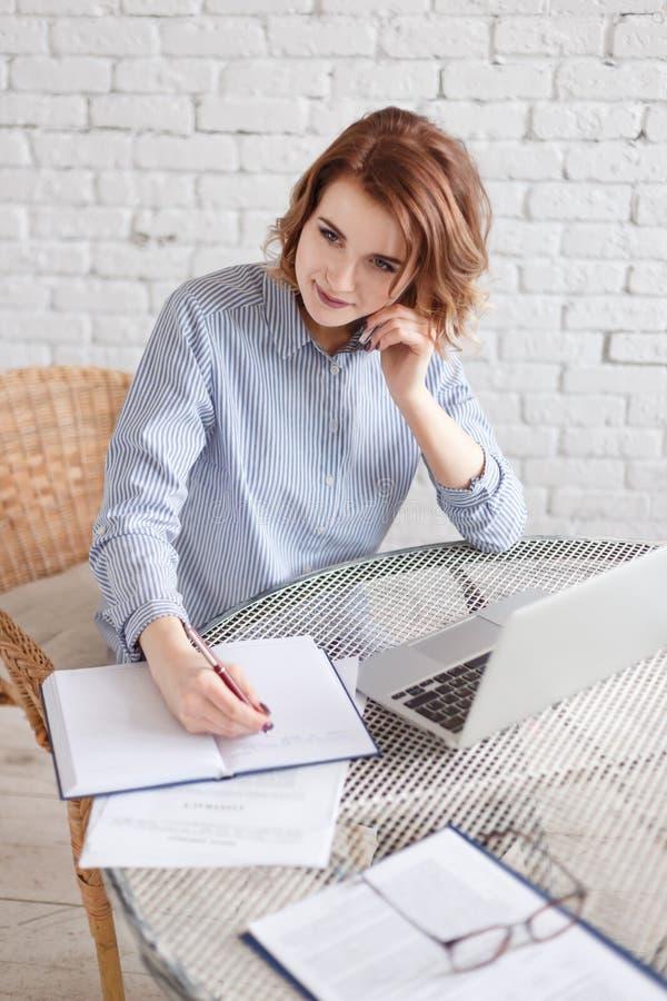 Biznesowa kobieta mówi na telefonie przy miejscem pracy obraz royalty free