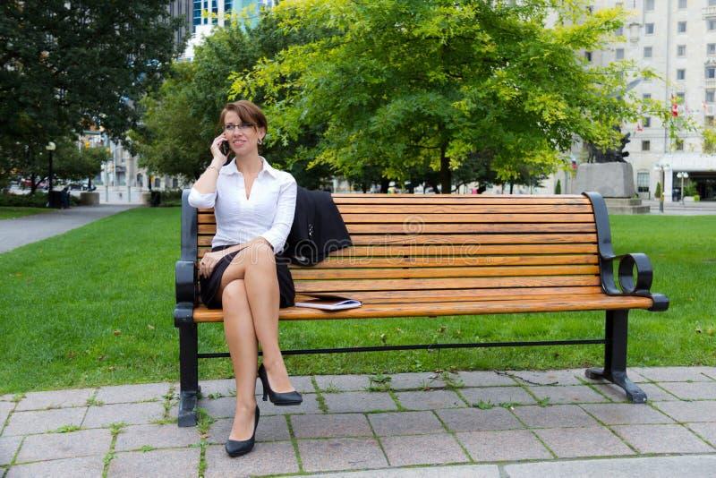 Biznesowa kobieta na parkowej ławce opowiada na telefonie obrazy stock