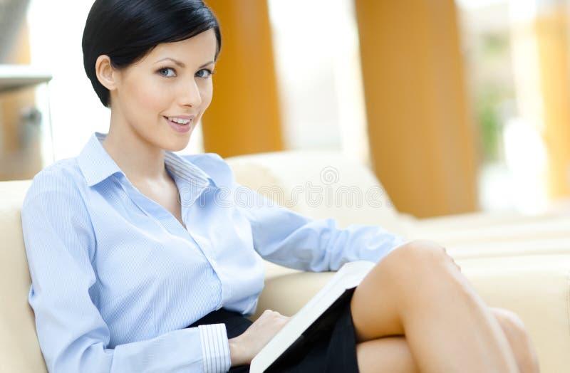 Biznesowa kobieta odpoczywa przy biały skóry kanapą zdjęcia royalty free
