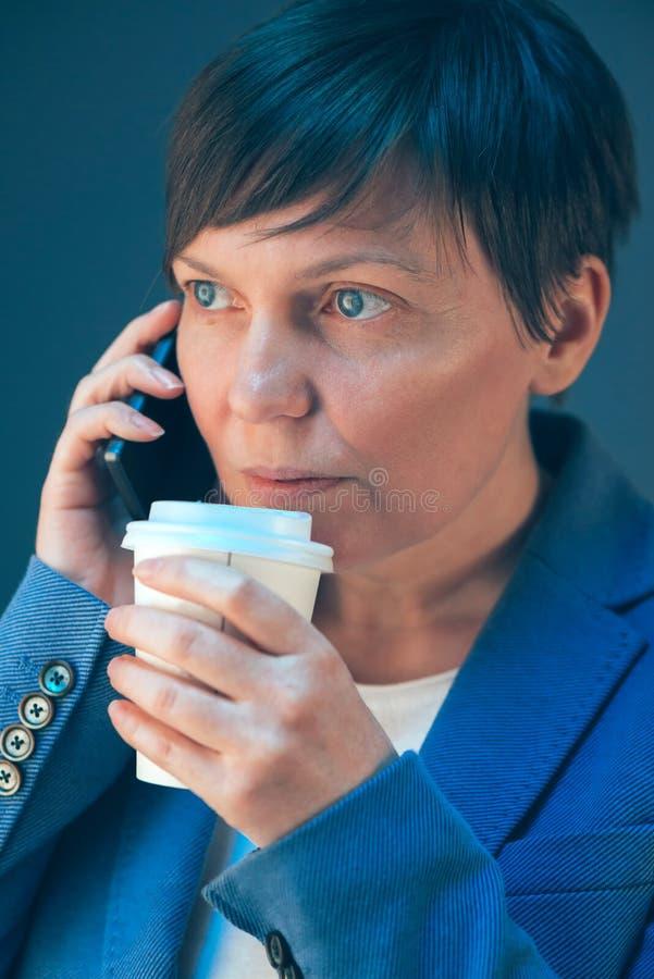 Biznesowa kobieta opowiada na telefonie komórkowym i pije kawę obraz royalty free