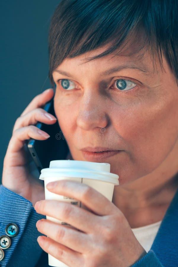 Biznesowa kobieta opowiada na telefonie komórkowym i pije kawę fotografia stock