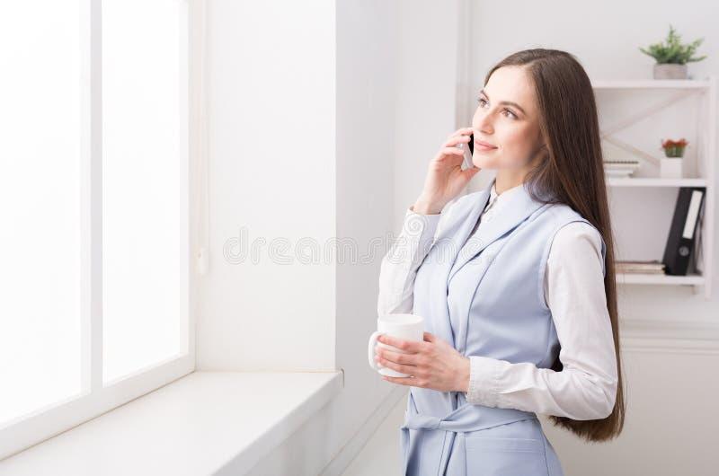 Biznesowa kobieta opowiada na telefonie przy okno obrazy royalty free