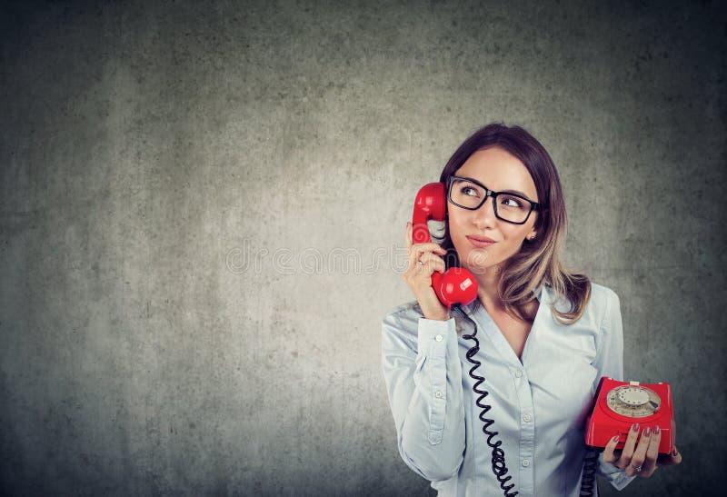 Biznesowa kobieta ostrożnie słucha klient z staromodnym tellephone obrazy royalty free
