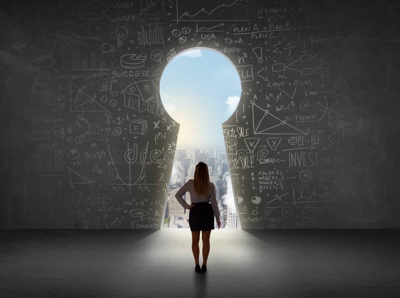 Biznesowa kobieta patrzeje keyhole z jaskrawym pejzażu miejskiego pojęciem zdjęcia royalty free