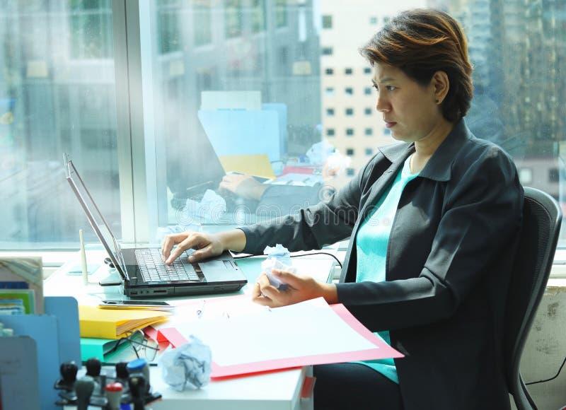 Biznesowa kobieta patrzeje laptop z poważną twarzą zdjęcia stock