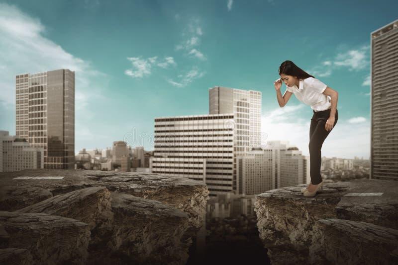 Biznesowa kobieta patrzeje w dół na łamanej drodze zdjęcie stock