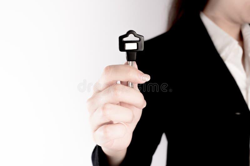 Biznesowa kobieta pokazuje czarnego klucz na białym tle kluczowy pojęcie sukces fotografia stock