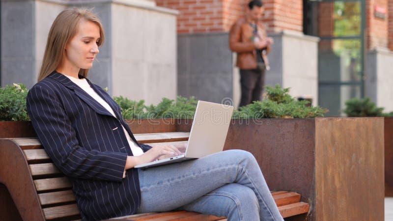 Biznesowa kobieta Pracuje na laptopie podczas gdy Siedzący Na zewnątrz biura zdjęcia stock