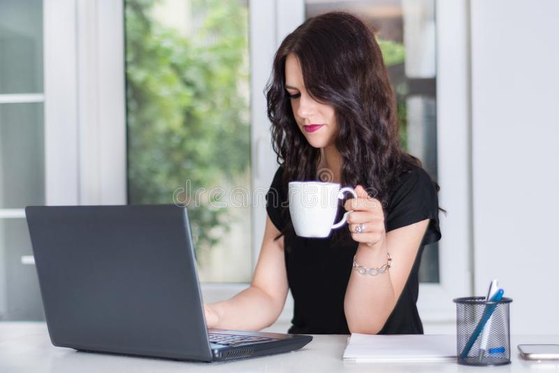 Biznesowa kobieta pracuje na laptopie przy biurowym biurkiem i pije filiżankę kawy zdjęcie stock