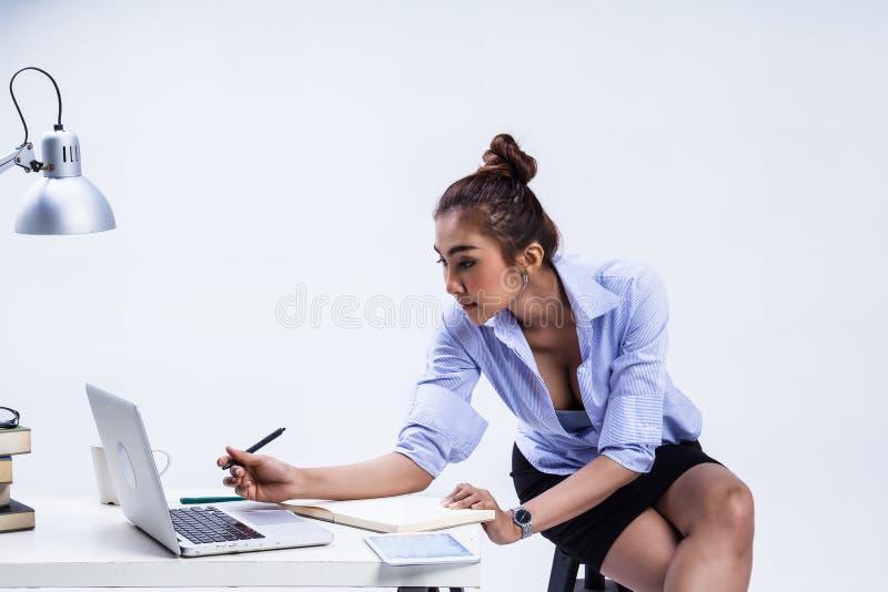 Biznesowa kobieta pracuje przy biurem, siedzi na czarnym krześle, chwyta pióro w ręce, przyglądający laptop szukać dane obraz royalty free