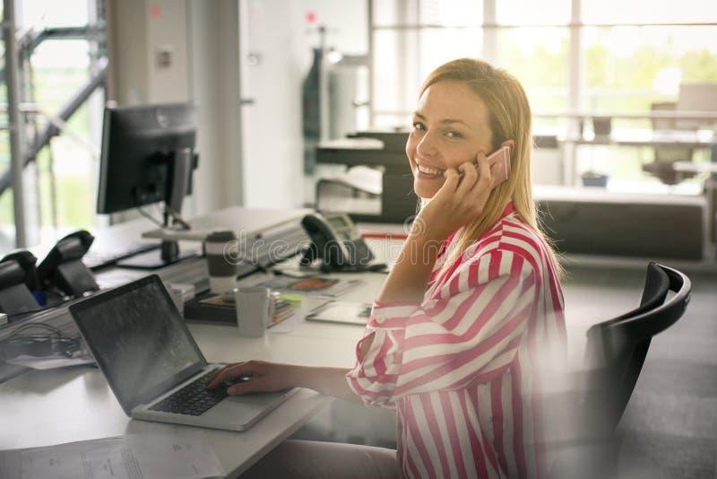 Biznesowa kobieta pracuje w biurze i opowiada na mądrze telefonie obrazy stock
