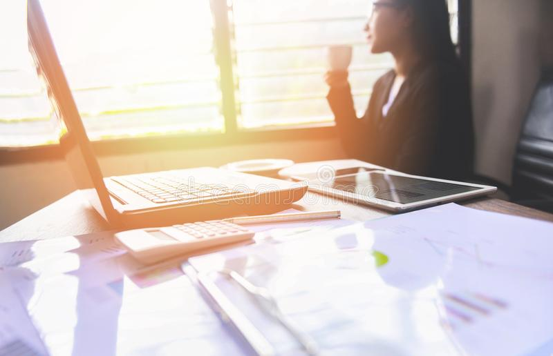 Biznesowa kobieta pracuje w biurze i trzyma filiżankę okno - Azjatycka kobieta pije kawowego obsiadanie przy jej pracującym miejs obraz stock