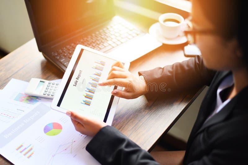 Biznesowa kobieta pracuje w biurze z sprawdzać biznesowego raport z kalkulatorem i kawą używać pastylki informatyki laptop obraz stock