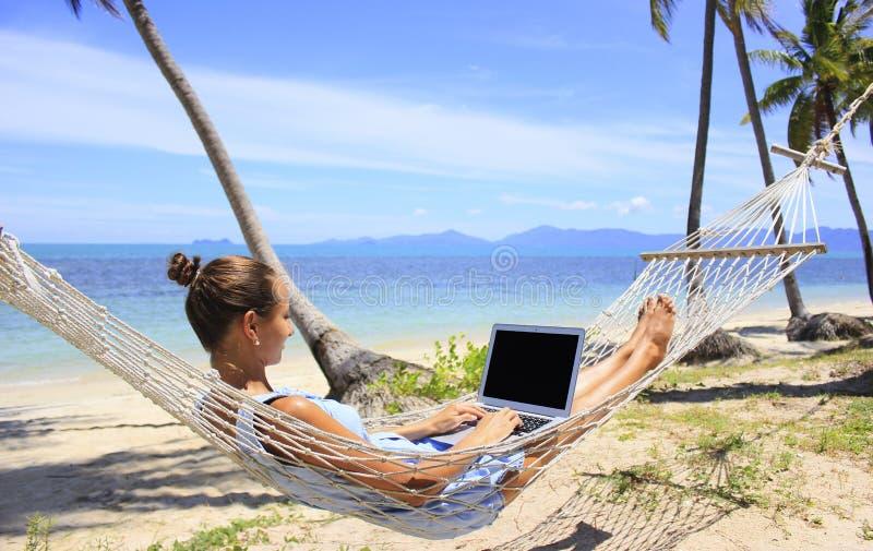 Biznesowa kobieta pracuje w hamaku na plaży zdjęcia stock