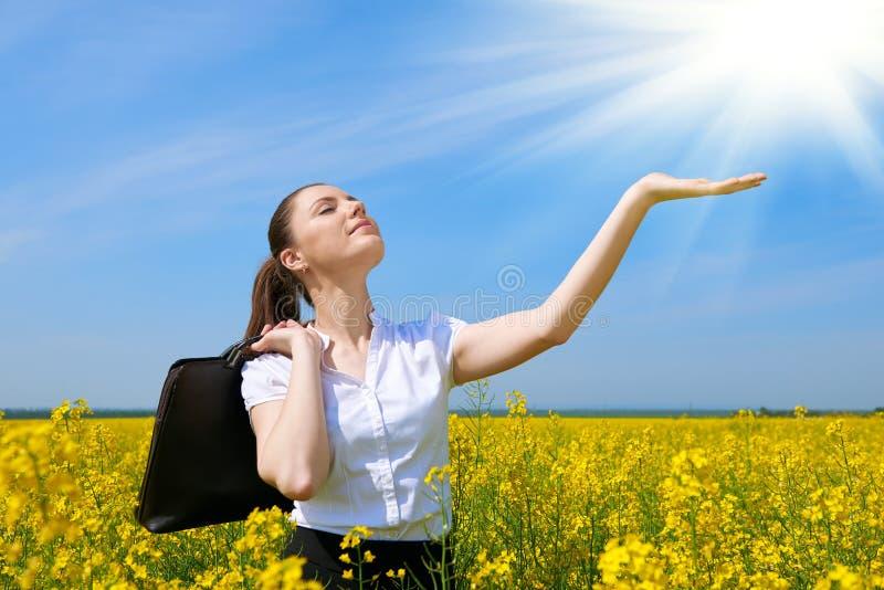 Biznesowa kobieta relaksuje w kwiatu pola plenerowym poniższym słońcu z teczką Młoda dziewczyna w żółtym rapeseed polu Piękny wio obrazy stock