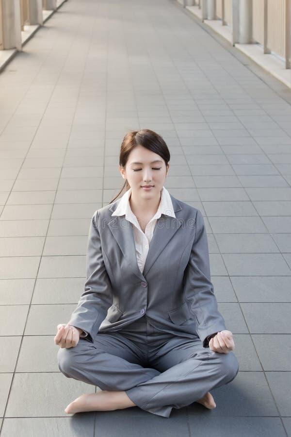 Biznesowa kobieta robi lotosowej pozyci zdjęcia stock