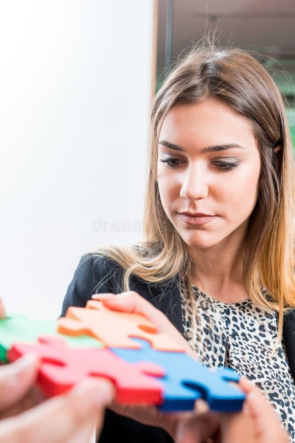 Biznesowa kobieta rozwiązuje wyrzynarki łamigłówkę z jej drużyną Drużynowy mienie obraz royalty free