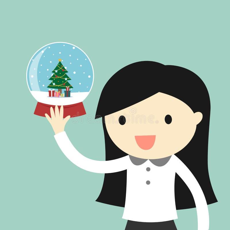 Biznesowa kobieta trzyma śnieżną kulę ziemską z choinką inside royalty ilustracja