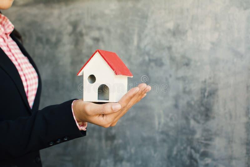 Biznesowa kobieta trzyma białego małego dom na ręce fotografia royalty free